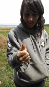 Emily checks out a small worm on her thumb, while simultaneously giving her approval with a thumbs up!